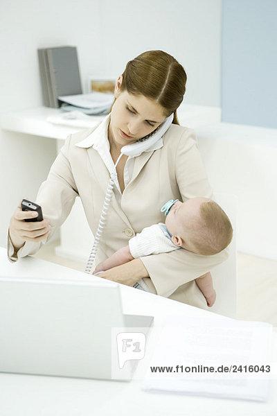 Junge berufstätige Mutter hält Baby  spricht am Festnetztelefon und schaut aufs Handy