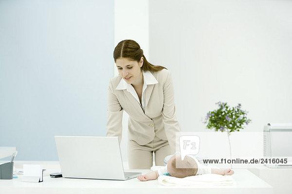 Junge berufstätige Mutter mit Laptop  Baby auf dem Schreibtisch liegend