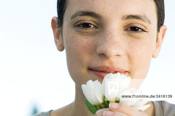 Young woman holding white flowers up to face