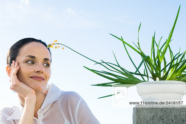 Woman with potted plant  smiling  low angle view