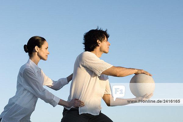 Paar zusammen im Freien  Mann hält Ball  Frau hält Mannes Hüften Paar zusammen im Freien, Mann hält Ball, Frau hält Mannes Hüften