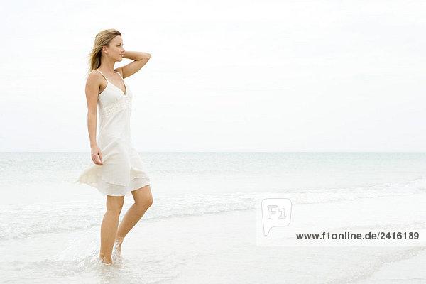 Frau in Sommerkleid Wandern am Strand  Seitenansicht Frau in Sommerkleid Wandern am Strand, Seitenansicht