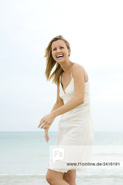 Woman in sundress at the beach  smiling  laughing