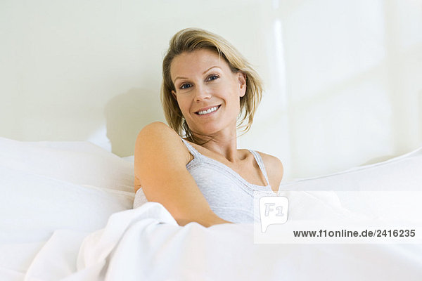 Frau sitzt im Bett  Lächeln in die Kamera
