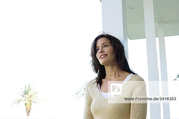 Frau stützte sich auf Veranda Säule  Lächeln  Untersicht