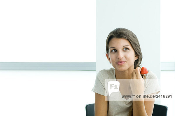 Teen girl holding strawberry  looking away