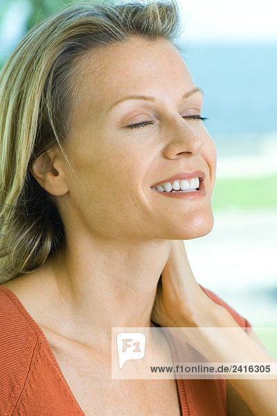 Woman smiling  holding neck  eyes closed