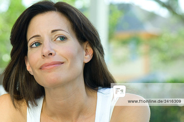Woman smiling  looking up  portrait