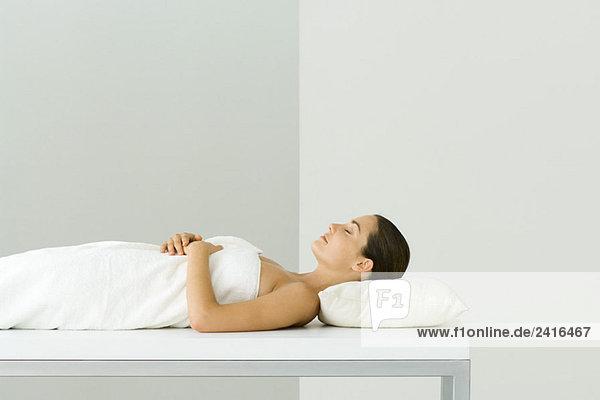 Frau liegend auf Massagetisch  Augen geschlossen
