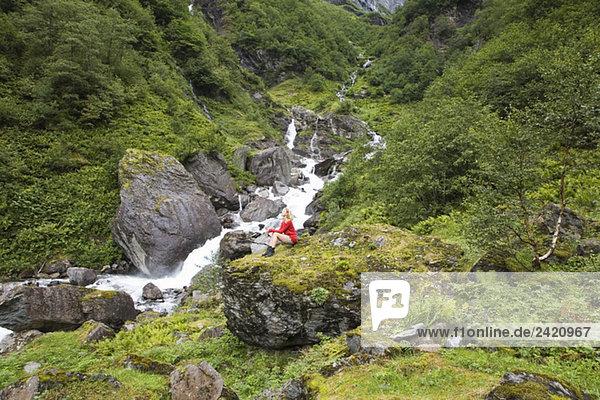 Frau entspannt am Wasserfall