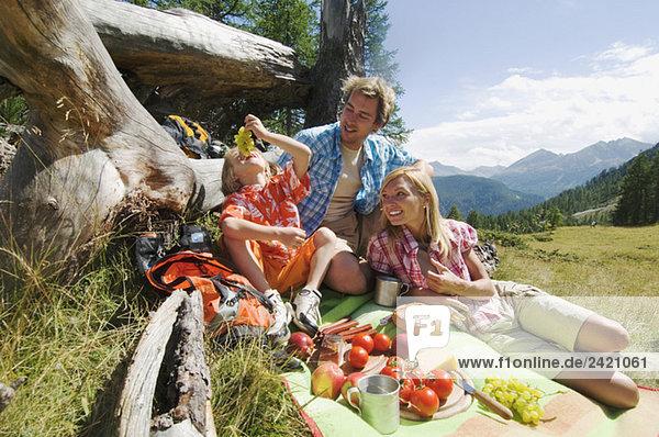 Österreich  Salzburger Land  Eltern und Sohn (8-9) beim Picknick