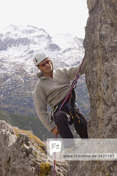 Austria  Salzburger Land  Man climbing on rock face