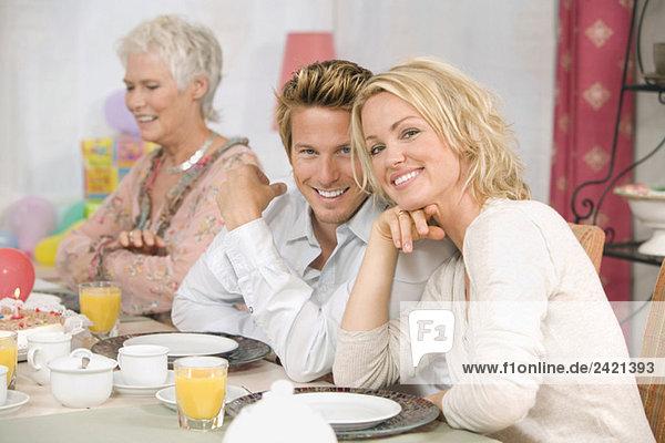 Familie am Esstisch  lächelnd