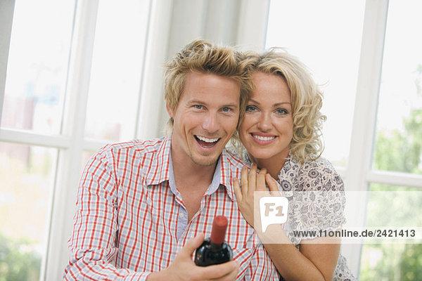 Junges Paar mit Weinflasche  lächelnd  Portrait