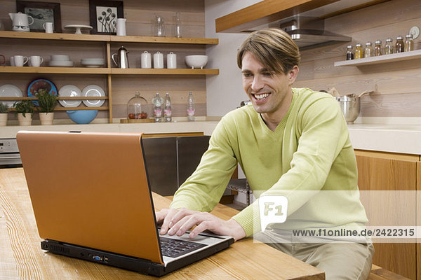 Junger Mann in der Küche sitzend mit Laptop  Portrait