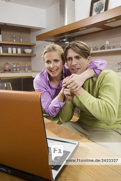Junges Paar in der Küche  Laptop schauen  Portrait