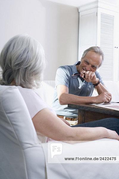 Seniorenpaar im Wohnzimmer sitzend  lächelnd  Portrait