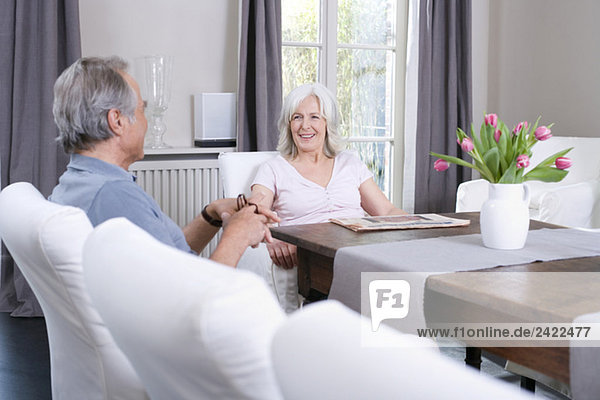Seniorenpaar am Tisch im Wohnzimmer sitzend  lächelnd  Portrait