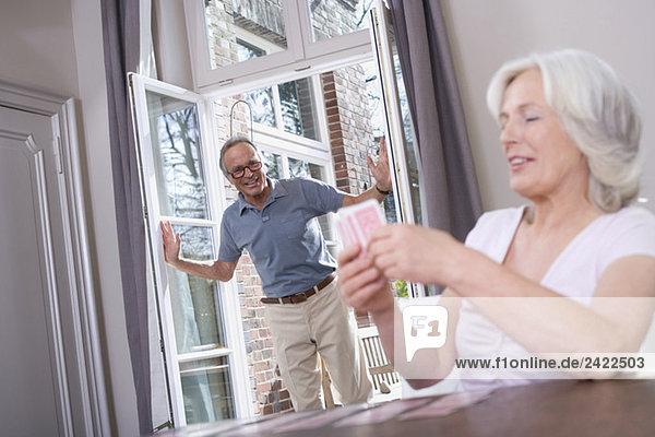 Senior Frau spielt Solitär  Senior Mann lehnt sich in die Tür  Portrait