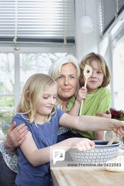 Enkelin (8-9) beim Teigmischen in der Schüssel  Portrait