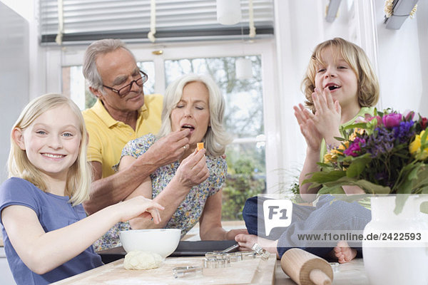 Großeltern und Enkel (8-9) in der Küche  Porträt