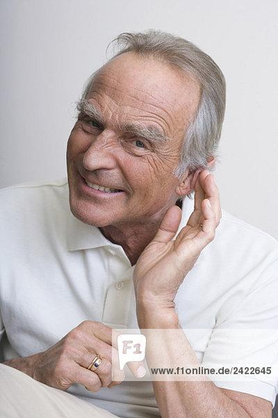 Senior Mann mit Hand an Ohr  lächelnd  Portrait