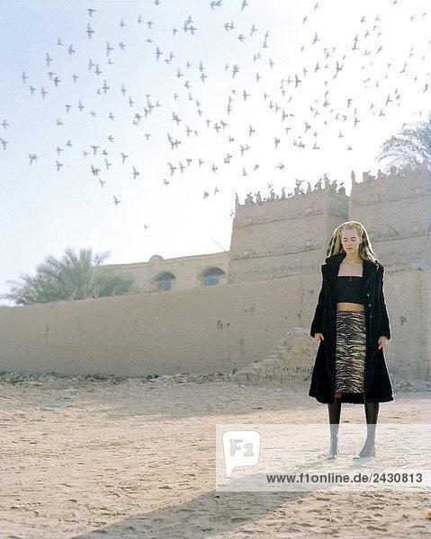Junge Frau steht vor einem Gebäude