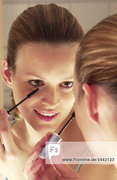 Nahaufnahme Frau Anwendung Mascara und lächelnd