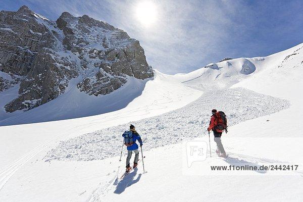 Rückansicht des zwei Skifahrer zu Fuß mit den Skiern auf verschneiten Berg  Knallstein  Tennengebirge  Schneebrett  Tennengau  Salzburg  Österreich