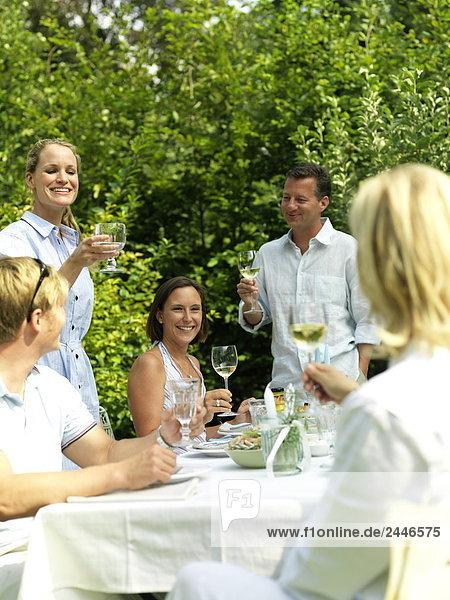 Fünf Menschen auf einer Gartenparty feiern