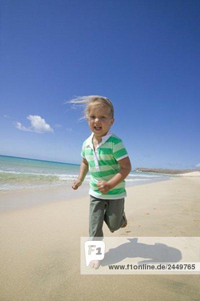 kleine Mädchen  die entlang sandiger Strand