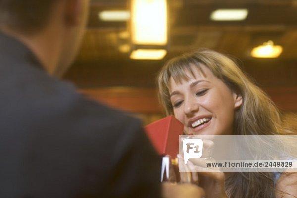 junge Frau im Restaurant von Freund bekommen