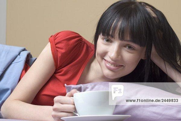 Portrait einer jungen Frau liegend im Bett mit Kaffeepause