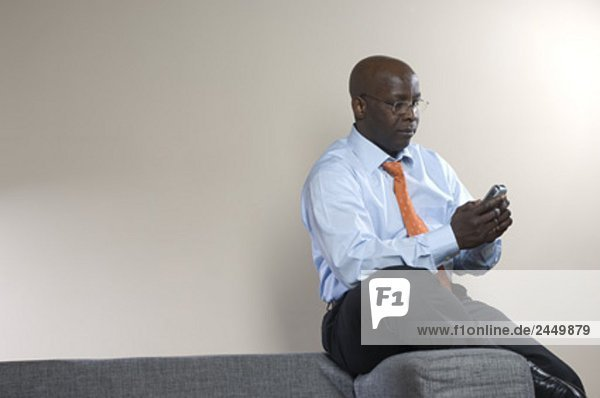 black businessman sitting on armrest of sofa checking mobile phone for text messages