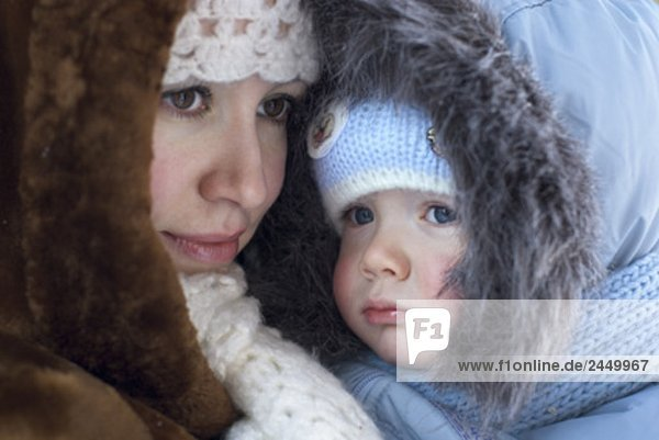 portrait of mother in winter clothes holding baby