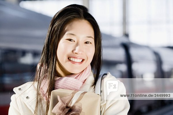 portrait of young japanese woman at train station holding present