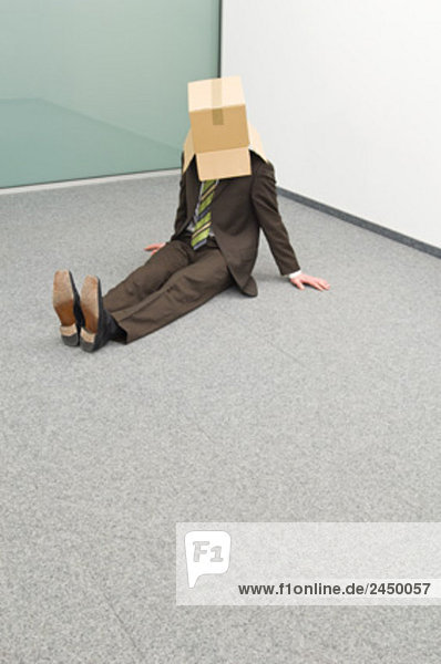 Businessman sitting in Ecke mit Umkarton über seinem Kopf