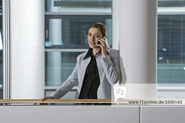 weibliche Executive am Handy im Korridor Offfice Gebäudes sprechen