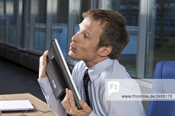 Portrait des Kaufmanns umarmt seine Computer-monitor