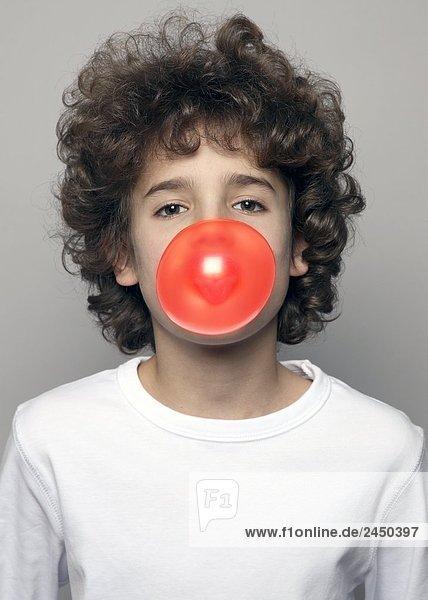 Porträt von Boy blowing Kaugummi