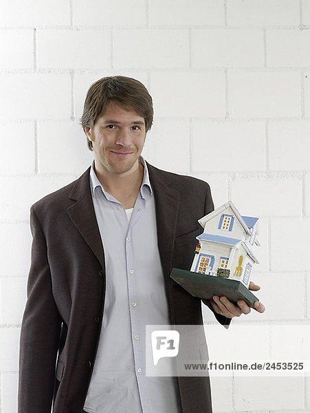 Mann mit Hausmodell