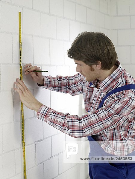Man wearing work wear with pencil and folding rule