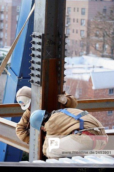 Eisen/Bauarbeiter sitzen auf Stahlträger anpassen Anker Schrauben