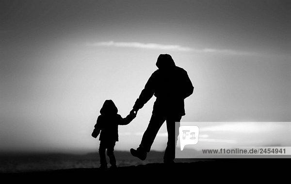 Vater und Tochter bei Sonnenuntergang am Strand entlang Schlendern. Silhouetten mit Hintergrundbeleuchtung