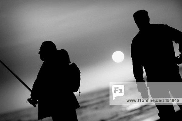 Silhouetten gegen die zwei Fischer bei Sonnenuntergang