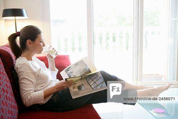 Entspannt Frau trinkt ein Glas Milch lesen ein Buch auf dem sofa