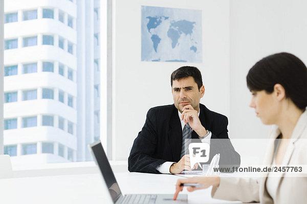 Führungskraft sitzt im Büro mit der Hand unter dem Kinn  Kollegin mit Laptop im Vordergrund