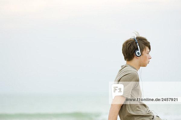 Teen boy sitting on beach listening to headphones  side view