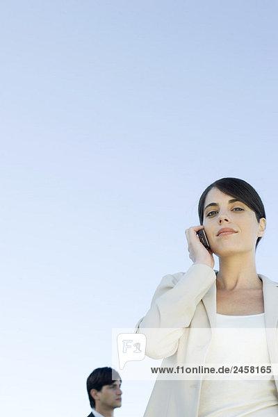 Geschäftsfrau mit Handy  lächelnd in die Kamera  Blickwinkel niedrig