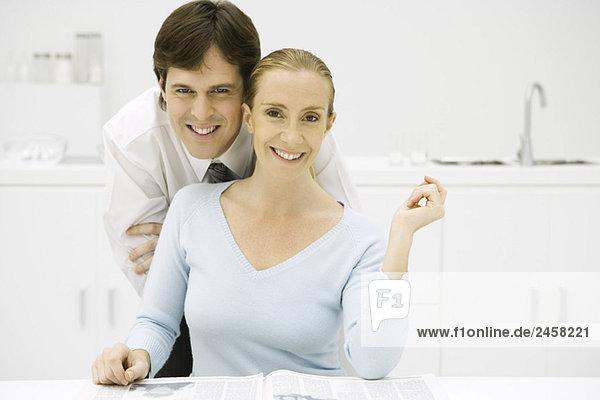Paar in der Küche  lächelnd vor der Kamera  Mann lehnt sich über die Schulter der Frau.